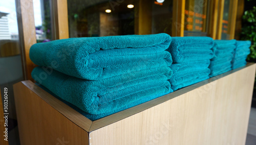Fotografía  Green rolled towels in pile on a counter for customer service at hotel, spa, swi