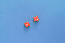 Red Pair Of Dice On A Blue Sur...