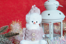 Cute Toy Snowman, Spruce Branches, Tinsel And A Candlestick On A Red Background....