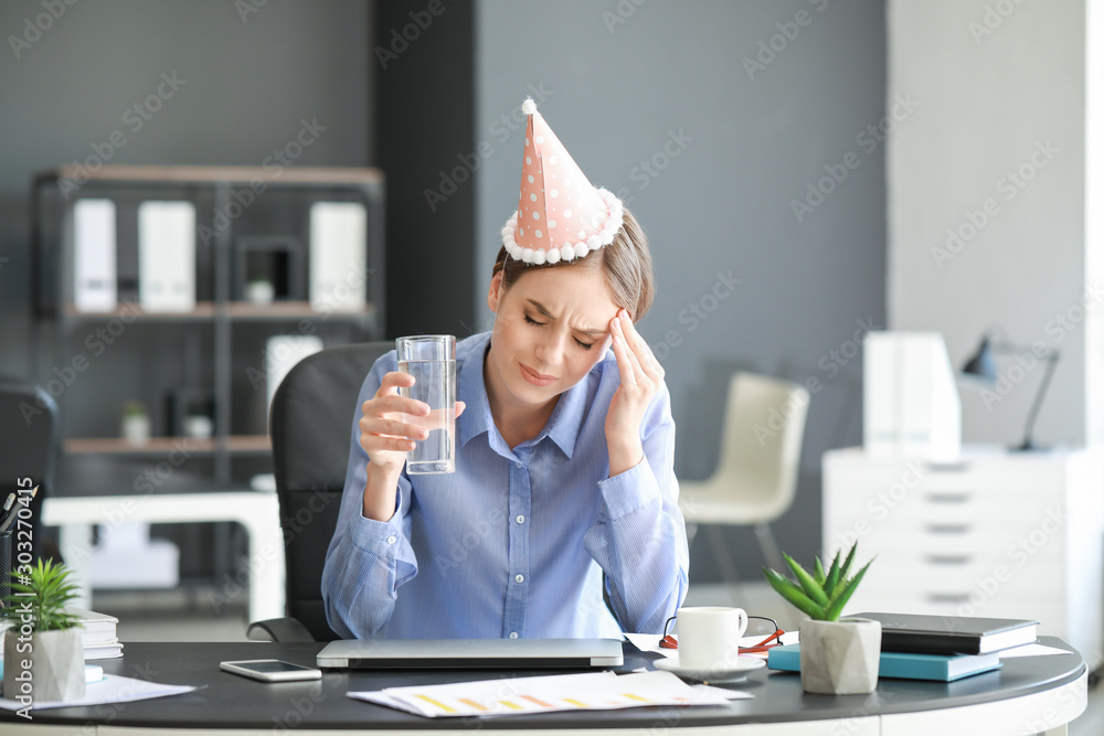 Fototapeta Young woman suffering from hangover in office