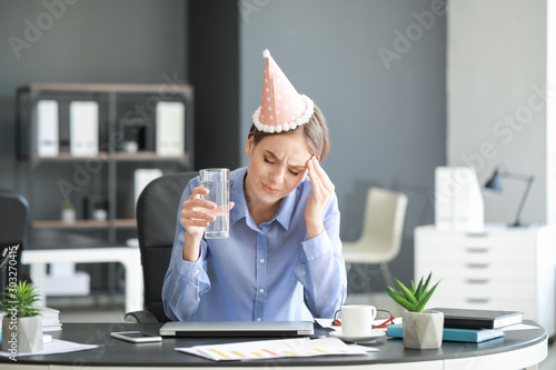 Obraz na plátně  Young woman suffering from hangover in office