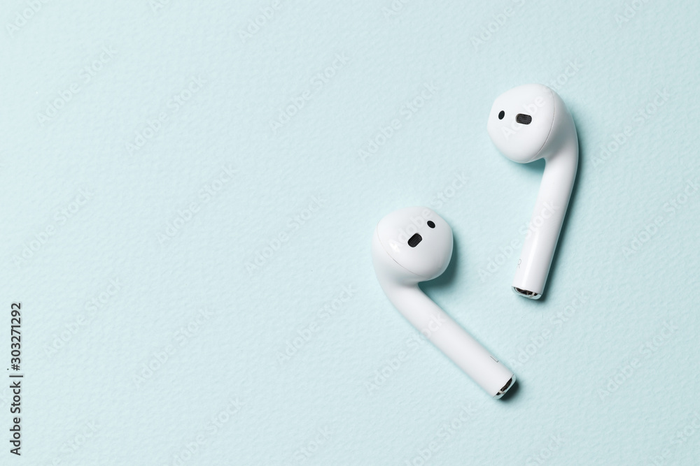 Fototapety, obrazy: Wireless headphones on a blue background with place for text.