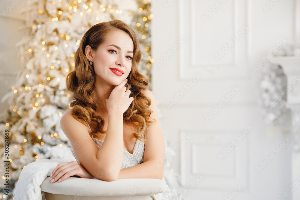 Fototapeta Young beautiful woman smiling and happy looking camera, hair styling makeup, white silver color on background of Christmas tree and fireplace bokeh