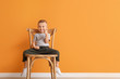 canvas print picture - Portrait of cute little boy sitting on chair and showing thumb-up gesture against color background