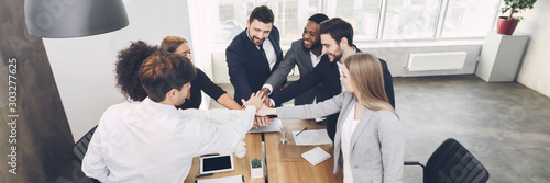 Young team joining hands involved in teambuilding activity Canvas Print