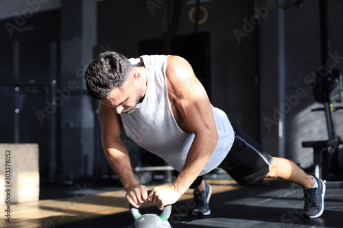 Fényképezés  Fit and muscular man focused on lifting a dumbbell during an exercise class in a gym