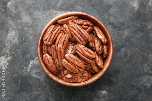 Fotomural Bowl with tasty pecan nuts on dark background