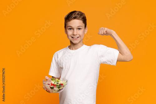 Teen boy with fresh vegetable salad demonstrating his biceps Wallpaper Mural