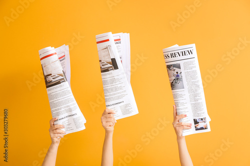 Fotografia Female hands with newspapers on color background