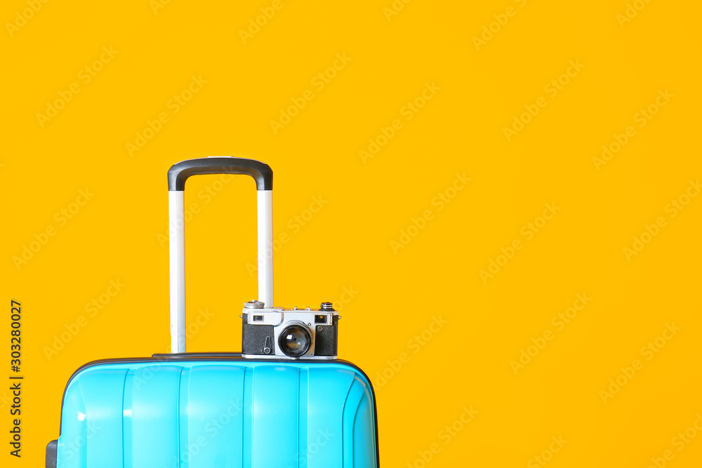 Fototapety, obrazy: Packed suitcase and photo camera on color background. Travel concept