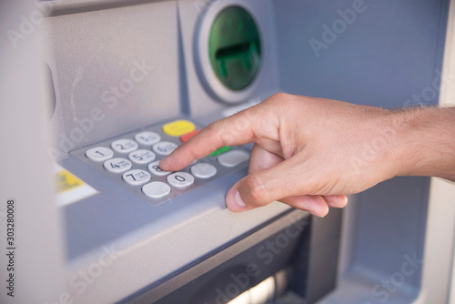 Fotografía  Close up of hand of a man using banking machine