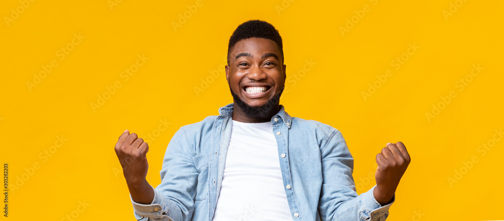 Fototapeta Happy african american man rejoicing success with clenched fists