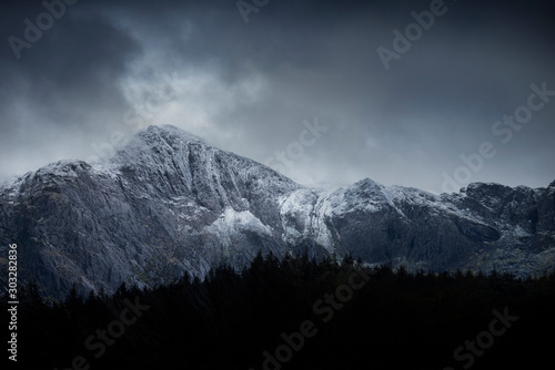 Foto auf Leinwand Dunkelgrau Stunning dramatic landscape image of snowcapped Glyders mountain range in Snowdonia during Winter with menacing low clouds hanging at the peaks