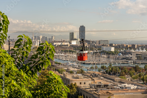 Obraz historic red cable car cabin, steel towers, harbor and Barcelona city, spain - fototapety do salonu