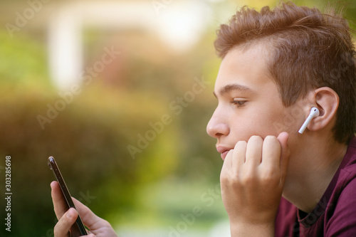 Close-up portrait of a thoughtful unhappy teenage boy with smartphone, outdoors Wallpaper Mural