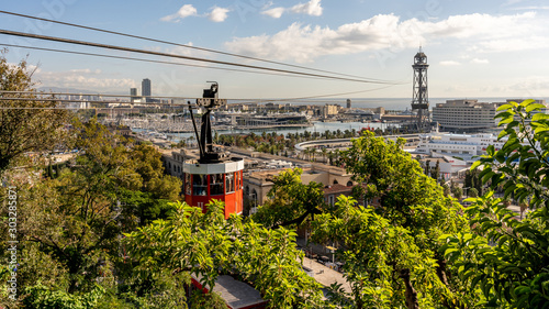 Obraz historic red cable car cabin with harbor and panorama of Barcelona city, spain - fototapety do salonu