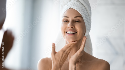 Happy lady look in bathroom mirror touching healthy face skin Canvas