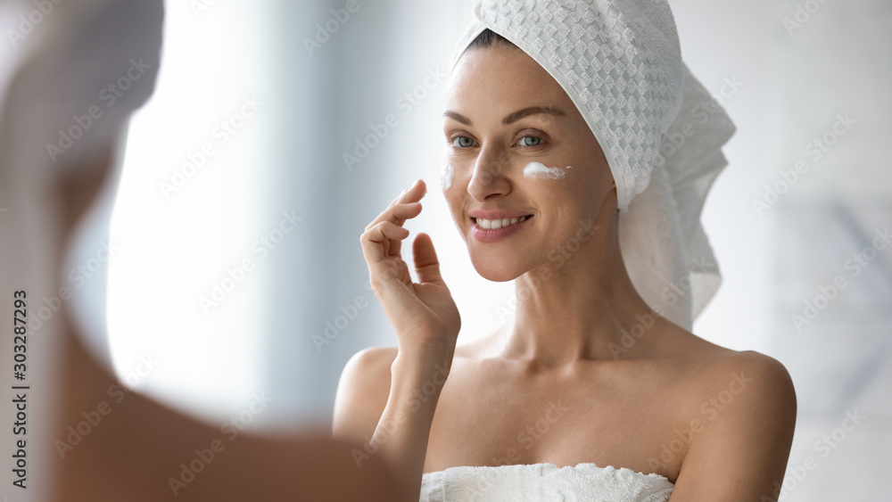 Fototapeta Smiling pretty lady put moisturizing facial cream look in mirror