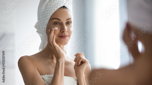 Attractive young adult woman applying facial cream looking in mirror Wallpaper Mural