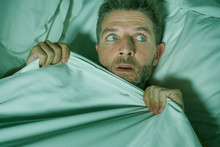 Stressed And Scared Man Alone In Bed Awake At Night In Fear After Having A Nightmare Feeling Paranoid Holding The Blanket In Funny Panic Face Expression
