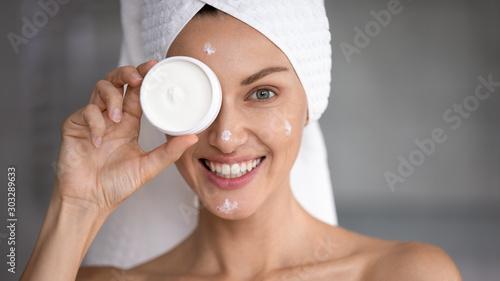 Cuadros en Lienzo Happy woman hold creme jar cover eye look at camera