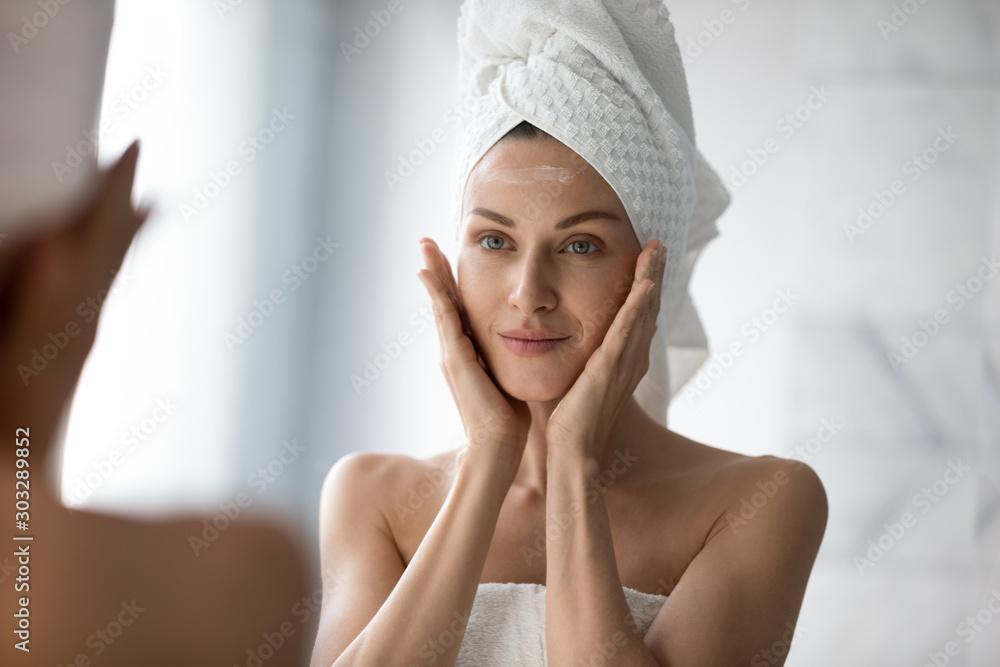 Fototapeta Beautiful young woman look in mirror massaging face applying cream - obraz na płótnie