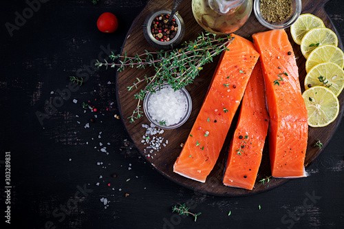 Fototapety, obrazy: Raw salmon fillet and ingredients for cooking on a dark background in a rustic style. Top view, flat lay