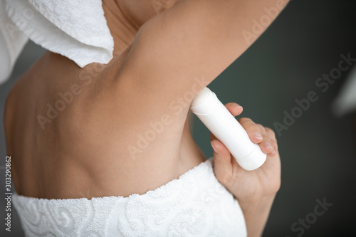 Photo Young lady wrapped in white towel apply antiperspirant in armpit