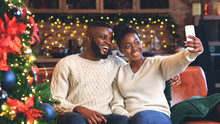 Cheerful Afro Couple Taking Selfie Near Christmas Tree At Home