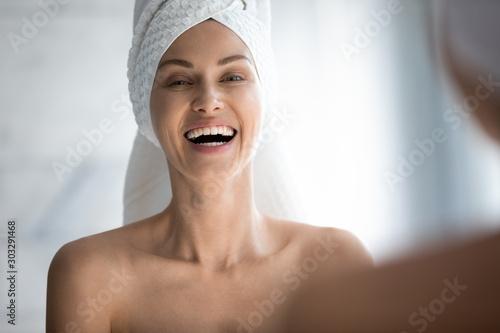 Cuadros en Lienzo  Happy woman towel on head laughing looking in mirror camera