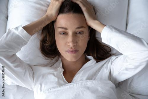 Obraz Disturbed woman lying awake in bed suffer from insomnia headache - fototapety do salonu