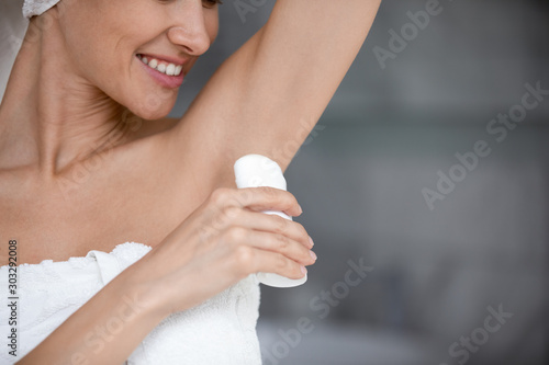 Fotomural  Smiling woman wrapped with towel applying antiperspirant stick in armpit
