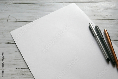 three pen on white paper background lay on white wooden background Fototapete