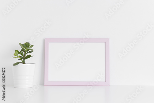 Fototapety, obrazy: Pink frame mockup with a crassula plant in a pot on a white table.Landscape orientation.