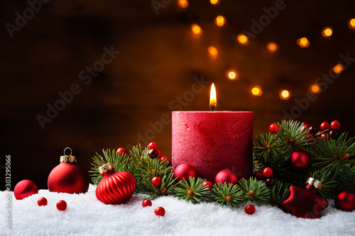 Advent candle, fir tree branches and holiday decorations in snow against light  garland background Fototapete