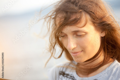 A portrait of a beautiful fair-haired young woman in windy weather near the ocean Canvas Print