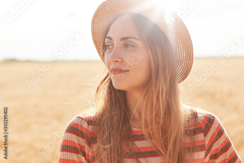 Outdoor shot of peaceful magnetic young lady looking aside, smiling, enjoying summer weather, spending time at wheat field, wearing casual clothes, sun shining brightly Fototapeta