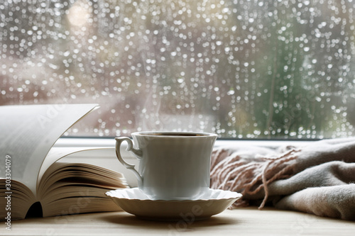 Porcelain cup with hot tea, soft blanket and open book by the window. - 303304079