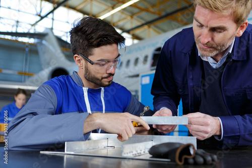 trainee aeronautics mechanic working at desk in hangar