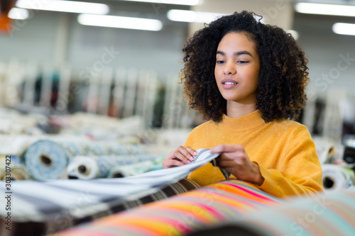 Obraz smiling woman choosing fabric in textile shop - fototapety do salonu