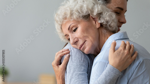 Grateful calm senior grandma mother embrace young adult daughter grandchild Fototapete