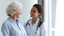 Smiling Young Female Nurse Assisting Happy Grandma Helping In Rehabilitation