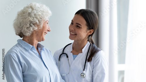 Fototapeta Smiling young female nurse assisting happy grandma helping in rehabilitation obraz