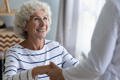 Happy grandma patient holding helping hand of caregiver getting up