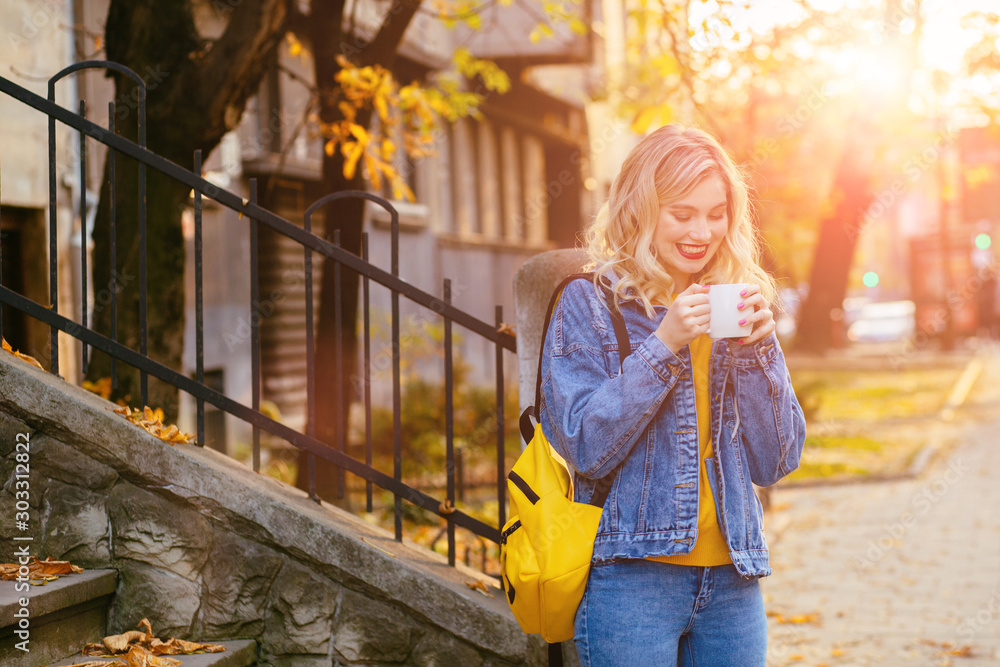 Fototapeta Front view outdoor full height portrait of female university student reading book drinking coffee sitting on old stairs on campus in fall autumn time season. Back to school concept.