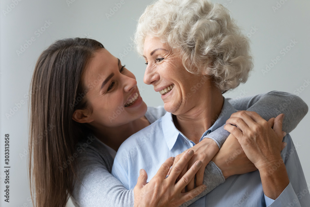 Fototapety, obrazy: Smiling young woman granddaughter embracing happy old granny or mom