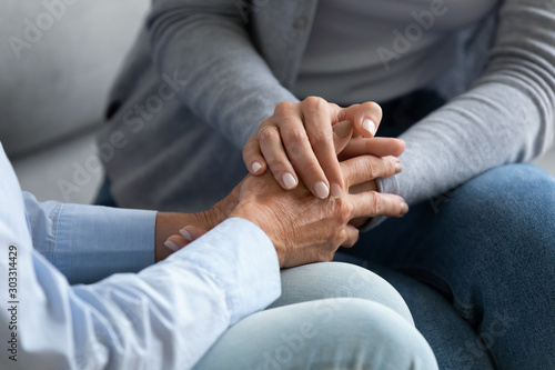 Young woman granddaughter hold old female grandma hand, closeup