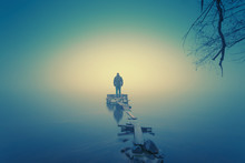 Lonely Man, Standing On The Wooden Jetty In The Autumn Foggy River With Stones Gangway.