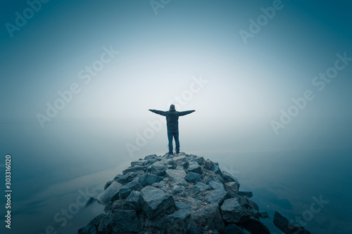 Foto auf AluDibond Blau türkis Man, standing on the stone heap at the foggy river bank. Long exposure shot.