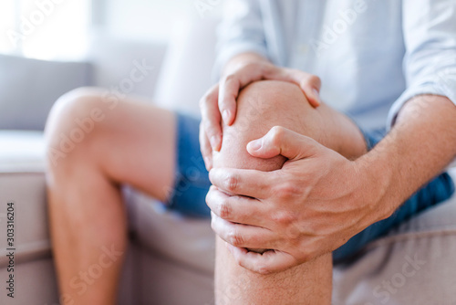 Fotografering Man suffering from knee pain sitting sofa